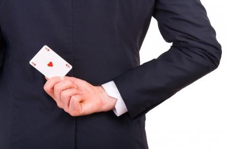 cheater: Businessman holding playing card behind his back  Stock Photo