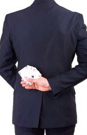 Businessman holding playing cards behind his back  photo