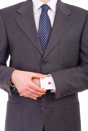 Hombre de negocios con tarjeta del as escondido bajo la manga photo