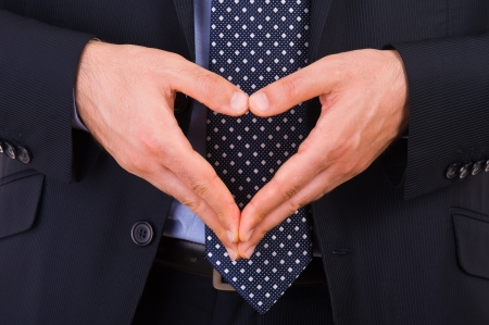 Businessman making heart symbol with hands. photo