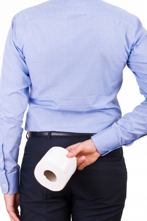 Businessman holding toilet paper behind his back. photo
