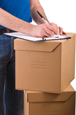 Delivery man writing in checklist on boxes photo