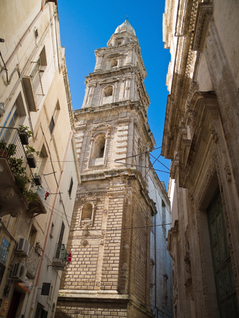 characteristic: This is a characteristic alley of Monopoli with Cathedral belltower. Apulia.