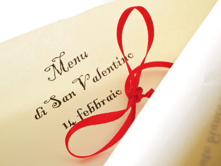 dinnertime: Valentines day unrolled parchment with red ribbon.