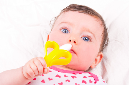 teether: Baby girl with rattle teether toy.