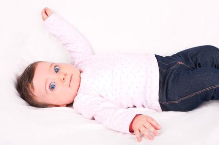 white sofa: Baby girl on white sofa. Stock Photo