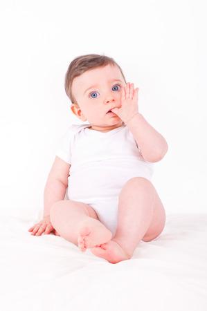 Baby-Mädchen mit dem Finger in den Mund.