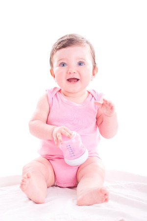 Baby girl with pink baby bottle. Stock Photo