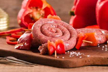 Raw sausage on wooden table.