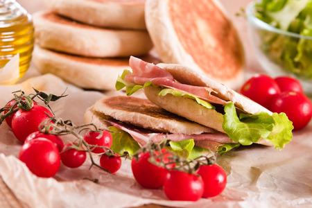 Tigella bread stuffed with ham and lettuce. Stock Photo