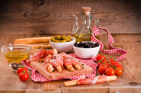 Grissini breadsticks with ham and olives.