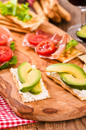 Crackers with ham and avocado.