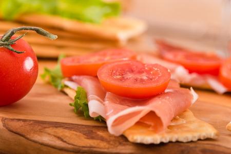Cracker con prosciutto e avocado. Archivio Fotografico - 81551781