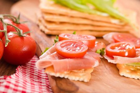 Cracker con prosciutto e avocado. Archivio Fotografico - 81551786