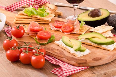 Cracker con prosciutto e avocado. Archivio Fotografico - 81551788