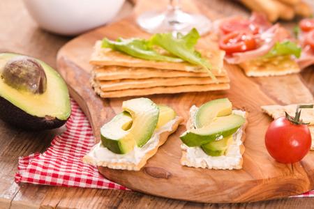 Cracker con prosciutto e avocado. Archivio Fotografico - 83759614