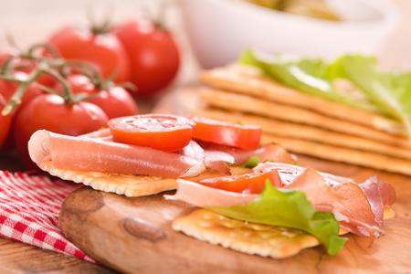 Cracker con prosciutto, pomodoro e avocado. Archivio Fotografico - 83759586