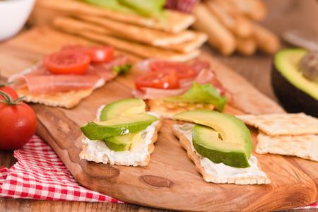Cracker con prosciutto e avocado. Archivio Fotografico - 85001330