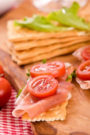 Cracker con prosciutto e avocado. Archivio Fotografico - 85070233