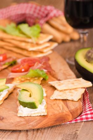 Cracker con prosciutto e avocado. Archivio Fotografico - 86045764