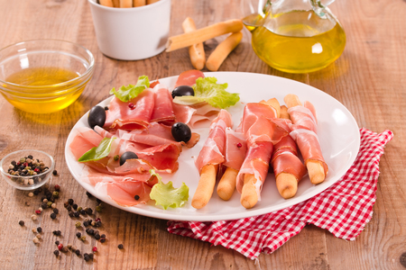 Grissini breadsticks with ham.  Stock Photo