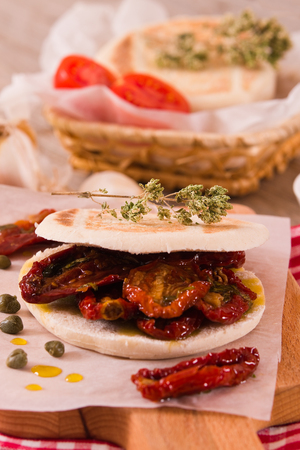 Tigella bread with sun-dried tomatoes. Archivio Fotografico - 119632719