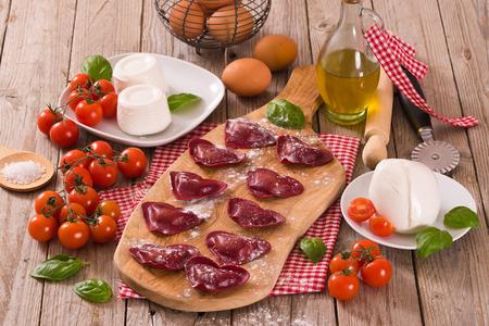 Red heart ravioli with tomato, mozzarella and basil. Banco de Imagens