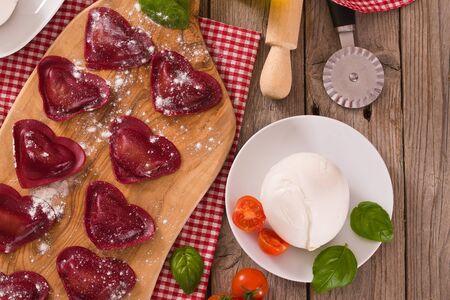 Red heart ravioli with tomato, mozzarella and basil. Imagens