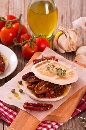 Tigella bread with sun-dried tomatoes. Archivio Fotografico - 125809876