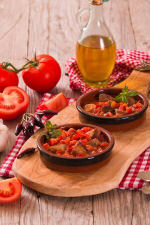 Marinated pork loin in tomato sauce.