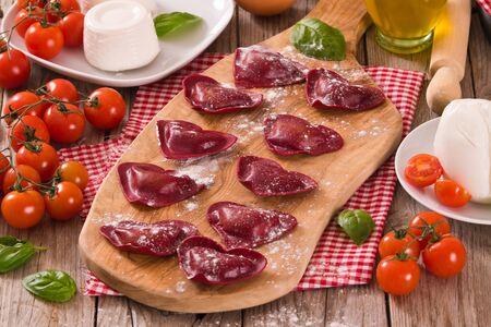 Red heart ravioli with tomato, mozzarella and basil.