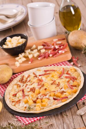 Tart with fried potato, raclette cheese and smoke flavour bacon.