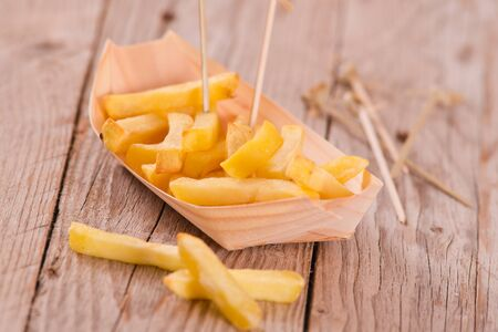 French fries with wooden background.