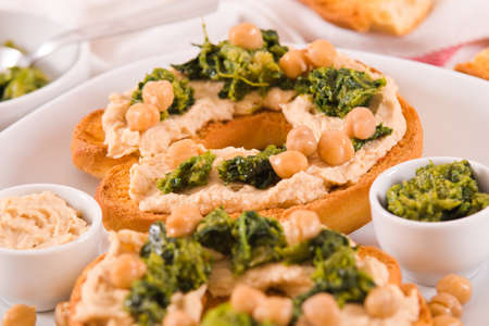 Friselle with turnip tops and hummus. Imagens