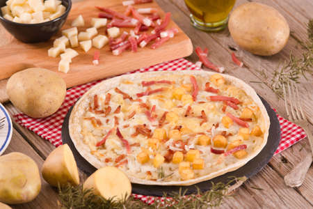 Tart with fried potato, raclette cheese and smoke flavour bacon. Reklamní fotografie