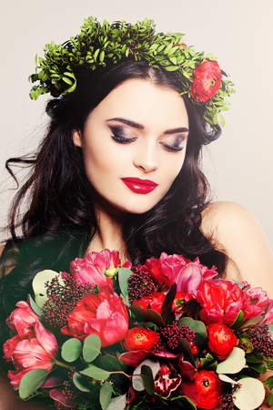 Beauty Fashion Portrait. Beautiful Woman with Curly Hair, Makeup and Flowers Stock Photo