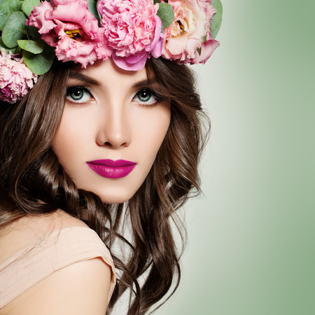 Beautiful Girl with Flowers Wreath. Long Permed Curly Hair and Fashion Makeup. Blossom Portrait of Pretty Young Woman with Pink Flowers. Stock Photo