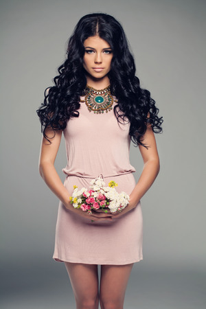 Fashion Model Girl in Little Pink Dress. Brunette Woman with Curly Dark Hair