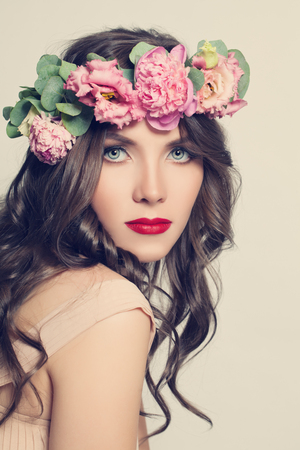 Beauty Girl with Flowers Hairstyle. Beautiful Young Woman Portrait with Summer Pink Pione Flowers. Long Permed Curly Hair and Fashion Makeup Stock Photo