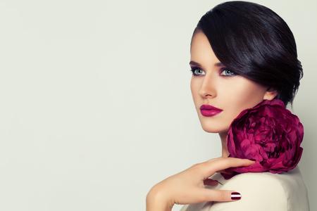 Elegant Woman Fashion Model with Burgundy Lips Makeup and Peony Flower Standard-Bild