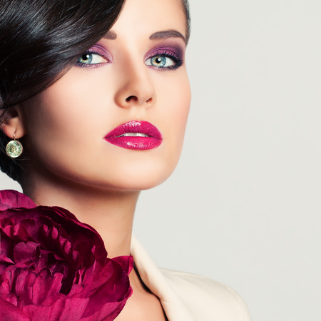 Closeup Portrait of Beautiful Woman Fashion Model with Makeup and Peony Flower. Cute Face Standard-Bild