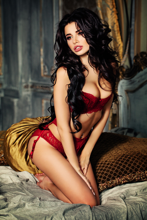 Beautiful alluring young brunette woman in red sexy lingerie