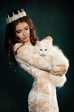 Beautiful young brunette woman with white cat Stock Photo