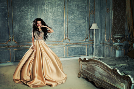 Glamorous Brunette Woman in a Bedroom in Royal Interior Stock Photo