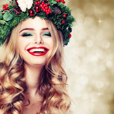 Christmas or New Year Beauty. Smiling Model Woman with Blonde Hair and Makeup Laughing. Girl with Blonde Curly Hairstyle on Party Background