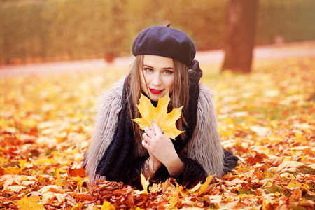 barrett: Autumn Portrait of Woman Fashion Model with an Fall Maple Leaf in her Hands  Stock Photo