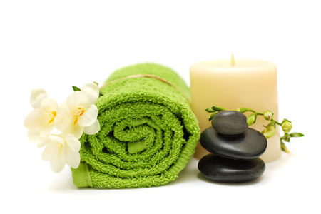 Spa concept - black stones, white flower, green towel Stock Photo