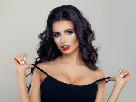 Beautiful Model with Curly Hairstyle, Red Lips Makeup and Black Top. Perfect Brunette Woman with Healthy Hair and Makeup
