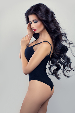 Beautiful Woman Fashion Model with Makeup and Blowing Hair wearing Black Swimsuit