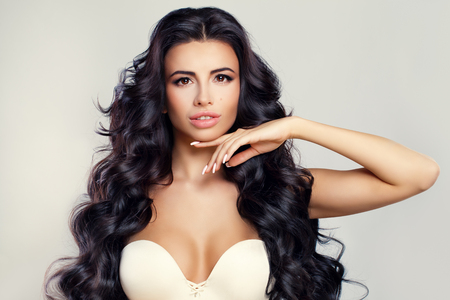 Perfect Model Woman with Long Curly Hairstyle Looking at her Hand